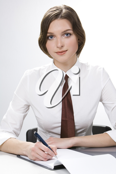 Portrait of pretty student wearing tie sitting at table with pen over notebook and looking at camera