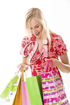 Portrait of happy smart woman looking into shopping bags