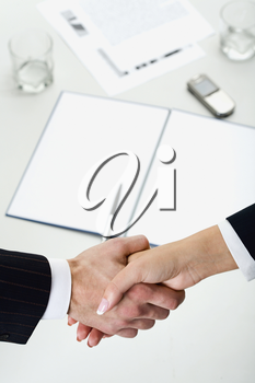 Woman and man shaking hands over paper, pen, phone, glasses on the background
