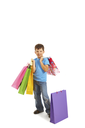 Image of smiling boy holding bags with presents or shoppings looking at camera
