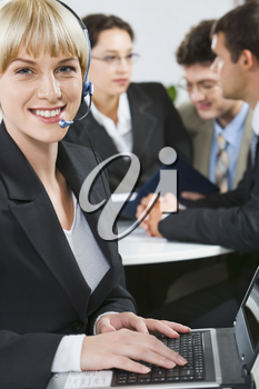 Successful woman with headset smiling on the background of three business people