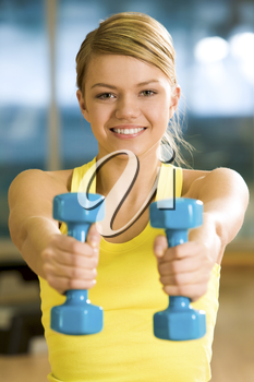 Happy girl stretching her hands with blue dumbbells during workout