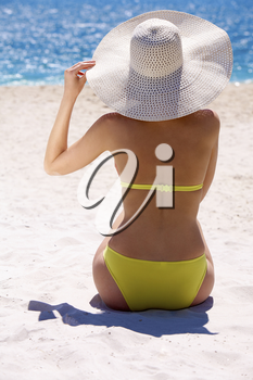 Rear view of young slim woman wearing swimwear and hat sitting on sandy beach