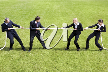 Photo of tug of war between business people