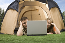Photo of modern couple lying on green grass and looking at laptop monitor in tent