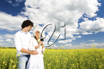 Image of happy amorous couple standing on the field and looking at each other with smiles