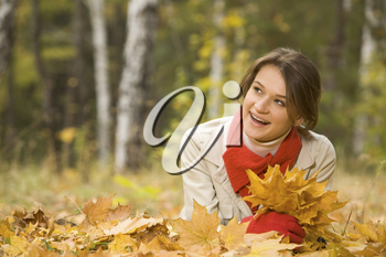 Portrait of pretty young female holding dry leaves in hand and smiling