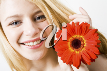 Close-up of cheerful young female holding red beautiful flower in hands and looking at camera