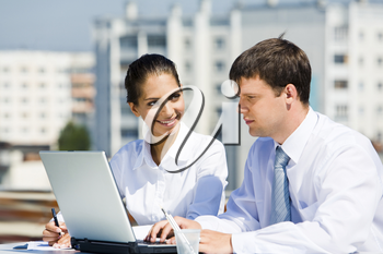 Portrait of two business partners working outside on background of houses