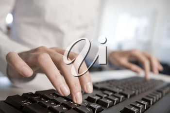 Image of female hands pressing computer keys at workplace