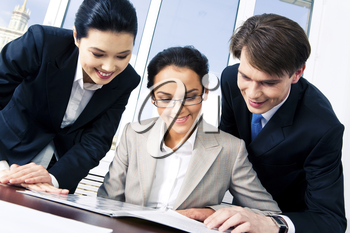 Close-up of three confident partners looking at business plan in the office at meeting