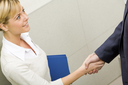Photo of confident businesswoman handshaking with her partner after signing contract