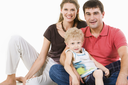 Photo of mother, father and son looking at camera on a white background