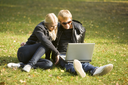 Photo of pretty girl and handsome guy sitting on grass and looking at laptop monitor outdoors