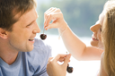 Portrait of pretty woman holding cherry with man near by