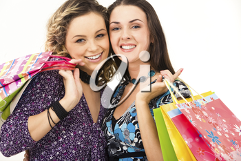 Close-up of two happy women carrying bags and looking at camera with smiles