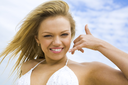 Portrait of beautiful blonde on background of cloudy sky