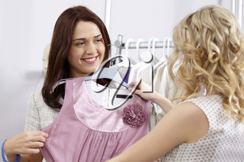 Image of pretty girl trying on tanktop with helpful assistant near by in the department store