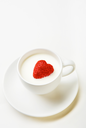 Strawberry heart inside cup of milk on porcelain saucer