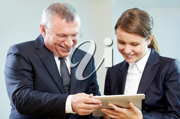 Boss and secretary looking at modern gadget with smiles during discussion