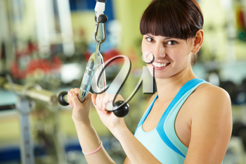 Photo of active girl pumping muscles on special equipment