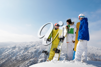 Portrait of handsome snowboarders standing on the mountain