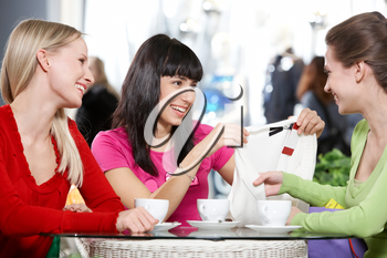 Three young women sitting in cafe and discussing new purchase