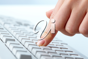 Close-up of a female finger pressing a key on computer keyboard