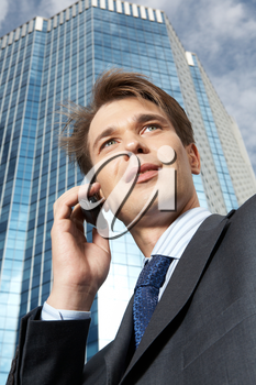 A businessman speaking on the telephone against an office building