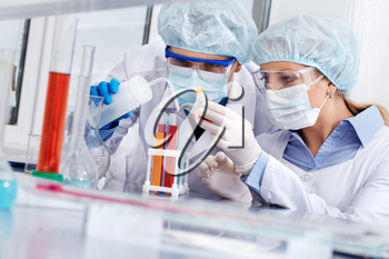 Serious clinicians studying liquids in laboratory