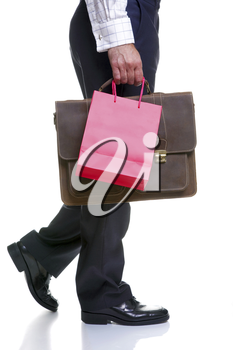 Legs of a man carrying a red gift bag and briefcase, isolated on a white background.