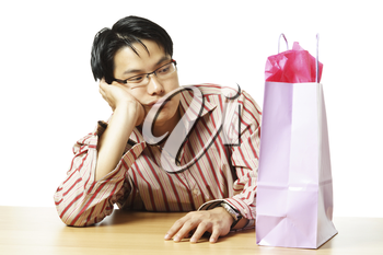 An isolated shot of a sad young man with a shopping bag