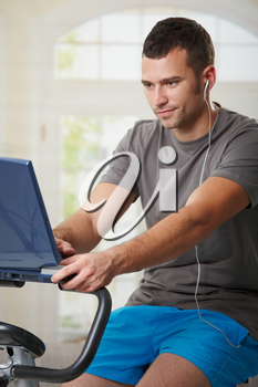 Man sitting on stationary bike at home, using laptop computer and listening music.