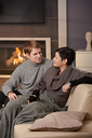 Young couple hugging on sofa in front of fireplace at home, looking at each other, smiling.