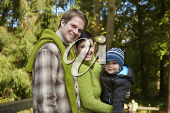 Portrait of happy family of three smiling at camera on sunny day in park.