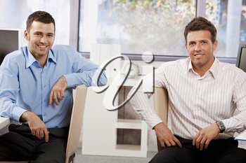 Two happy businessmen sitting at desk in office,  looking at the camera smiling.