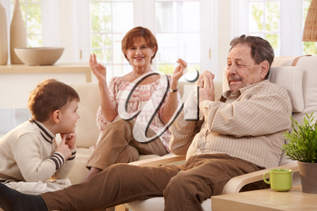 Grandparents with grandson sitting in living room at home having fun together.