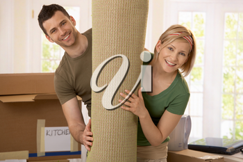 Portrait of couple moving house, holding carpet rolled up, smiling.