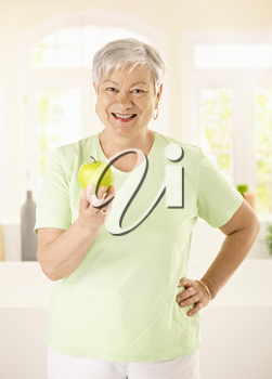 Healthy elderly woman holding apple, looking at camera, smiling.