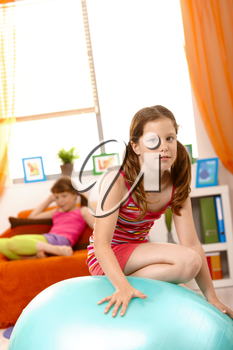 Young girl climbing on gym ball in living room, friend in background on sofa.