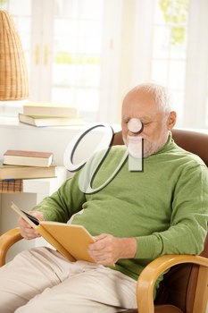 Older man sitting in armchair by window, relaxing at home, reading book, smiling.