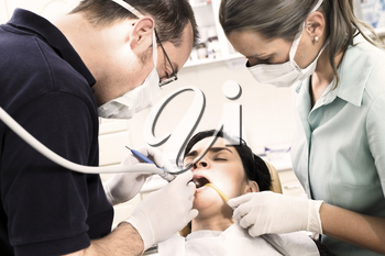 Young female patient takes a dental attendance in the dentist's office.