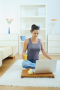 Casual young woman using laptop computer, sitting on floor in living room.