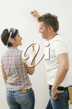 Couple smiling at each other while painting wall white, woman holding paint brush.