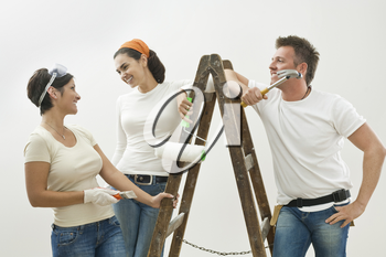 Young couple and friend painting new home, smiling at each other. Isolated on white background.