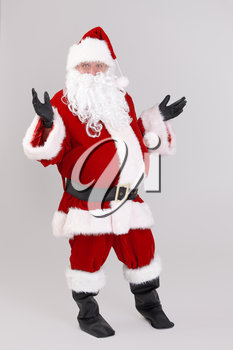 Full size portrait of surprised Santa Claus looking at camera, isolated on gray background.