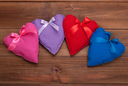 Hearts with ribbons of different colors on a wooden background.