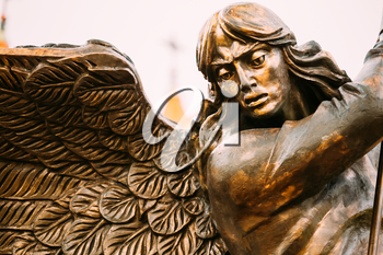 Close Up Detail Of Statue Of Archangel Michael With Outstretched Wings, Thrusting Spear Into Dragon Before Red Catholic Church Of St. Simon And St. Helena On Independence Square In Minsk, Belarus