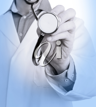 Close up of a Doctor's hand, holding a stethoscope outstretched towards the viewer, medical blue