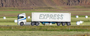 White trruck driving through a rural area - Express